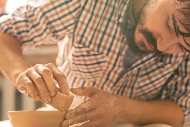 Mestre preciso da cerâmica usando uma esponja para suavizar as bordas do pote de barro enquanto trabalha sobre um dos itens de cerâmica