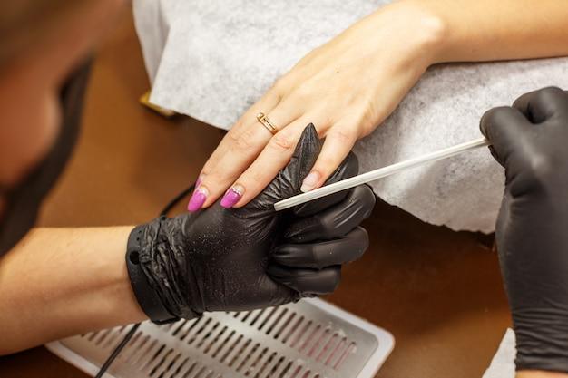 Mestre profissional de manicure faz as unhas para o cliente.