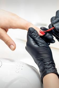 Mestre profissional de manicure pintando unhas femininas com esmalte vermelho em salão de beleza