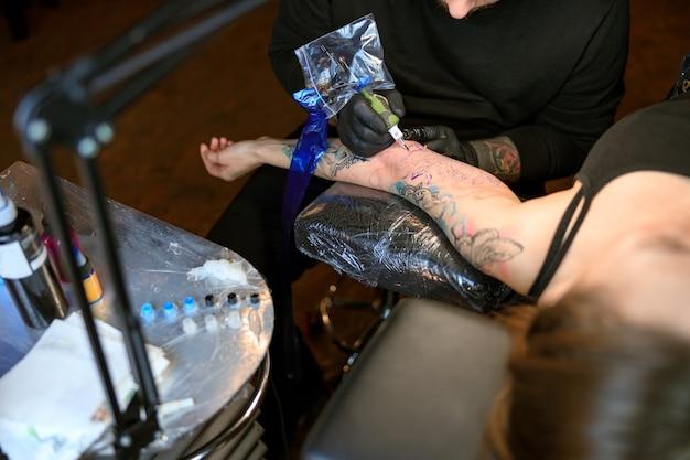 Mestre profissional de tatuagem caucasiano barbudo trabalhando em um estúdio aconchegante