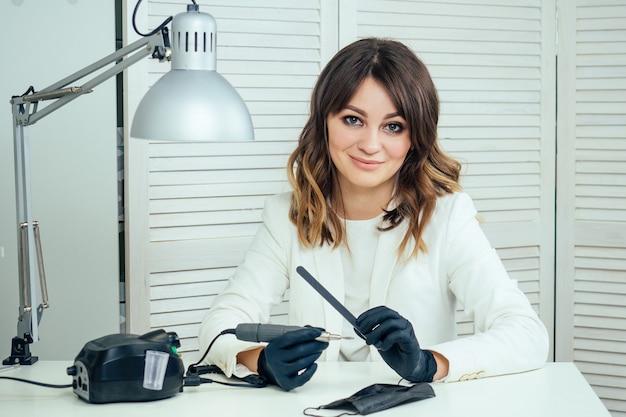 Mestre profissional jovem manicure atraente da mulher de manicure em uma jaqueta branca e luvas de borracha pretas prepara uma ferramenta de manicure de hardware de máquina para remover cutículas em um salão de spa de beleza.
