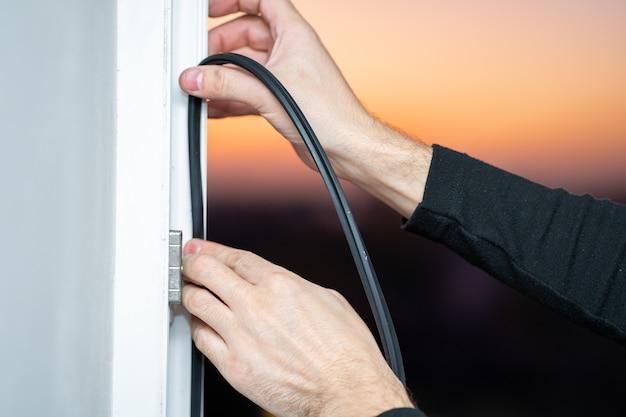 Mestre profissional na reparação e instalação de janelas, muda a junta de vedação de borracha nas janelas de pvc