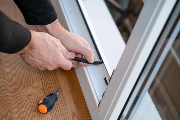 Mestre profissional na reparação e instalação de janelas, muda a junta do vedante de borracha nas janelas de pvc
