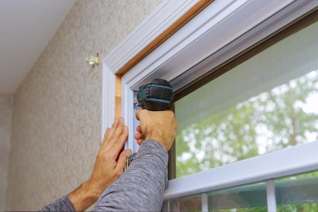 Mestre profissional para instalação de nova janela na casa durante a reforma da casa usa uma furadeira elétrica