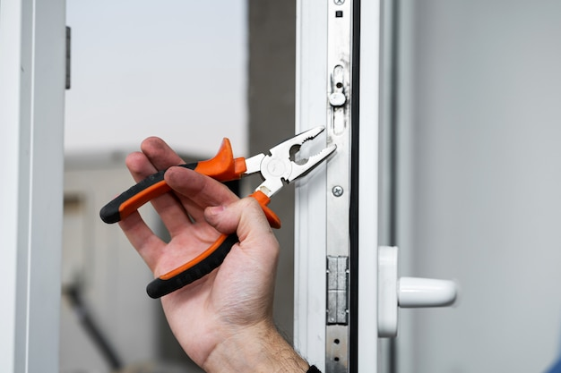 Mestre profissional para reparo e instalação de janelas, configura um sistema de abertura de janelas no modo inverno