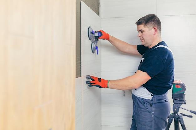Mestre profissional trabalhador masculino colocando ladrilhos de cerâmica na parede