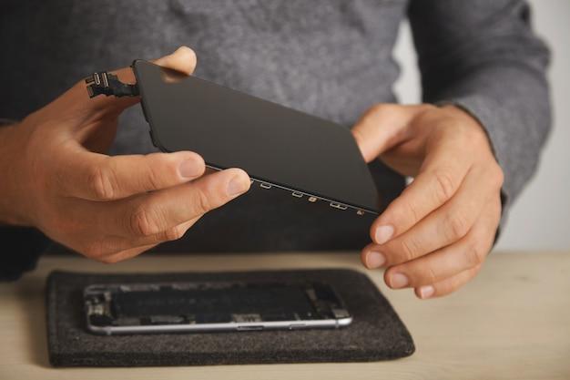 Mestre segura nova tela para substituição acima do smartphone desmontado em seu laboratório, close-up