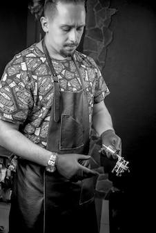 Mestre tatuador com uma pistola de tatuagem em um estúdio de oficina