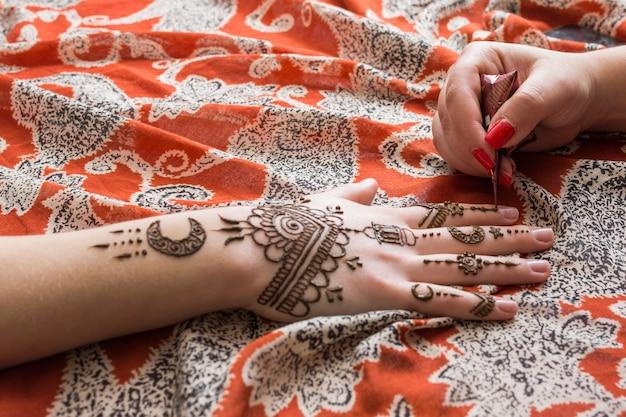 Mestre tatuagem tinta mehndi na mão da mulher