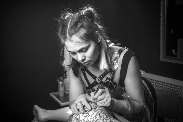 Mestre trabalhando em metralhadora profissional de tatuagem em salão de tatuagem