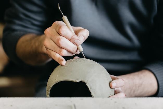 Mestre trabalhando em um modelo de escultura em argila