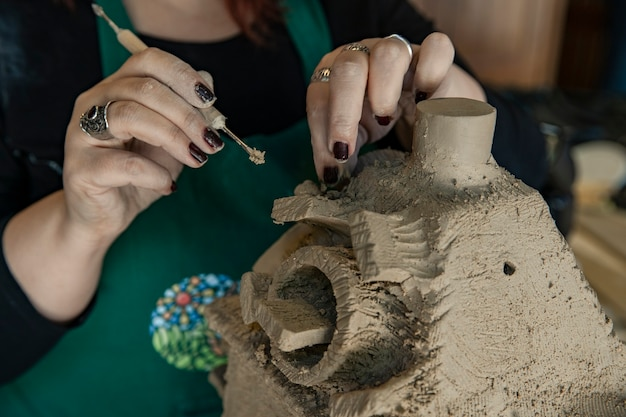 Mestre usando argila e fazendo uma escultura