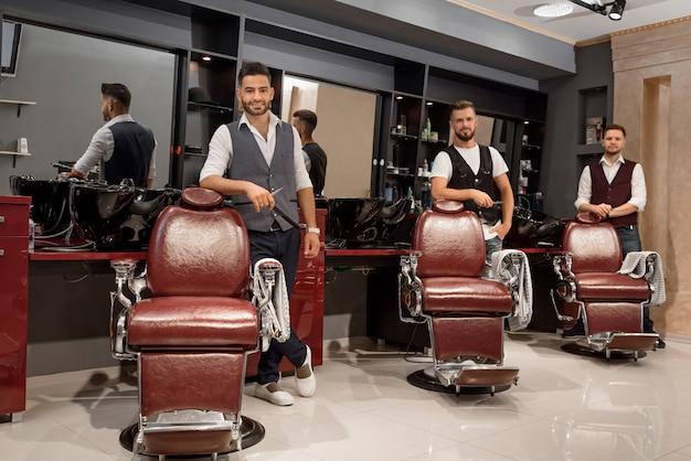 Mestres confiantes barbeiros em pé perto de cadeiras de cabeleireiro e posando.