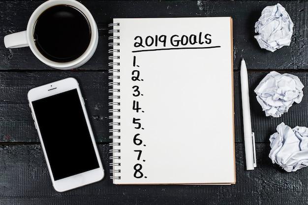 Meta de ano novo de 2019, plano, texto de ação no bloco de notas com acessórios de escritório.