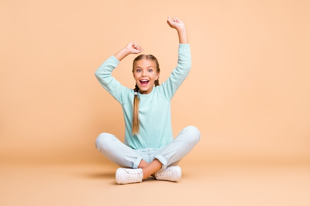 Meta! foto de corpo inteiro da linda mocinha levantando os punhos assistindo esporte jogo animado fã sentar chão pernas cruzadas usar suéter azul jeans calçado isolado parede bege