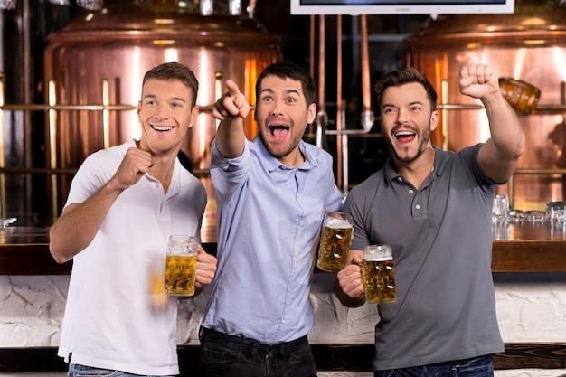 Meta! três homens felizes segurando canecas de cerveja e gesticulando enquanto assistem tv no bar