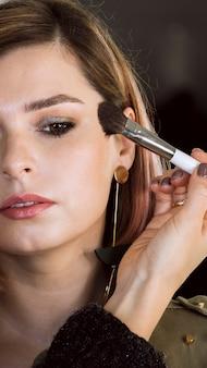 Metade da face do cliente de maquiagem