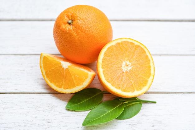 Metade da fatia de laranja fresca e frutas saudáveis da folha de laranja colhem conceito - fruta laranja