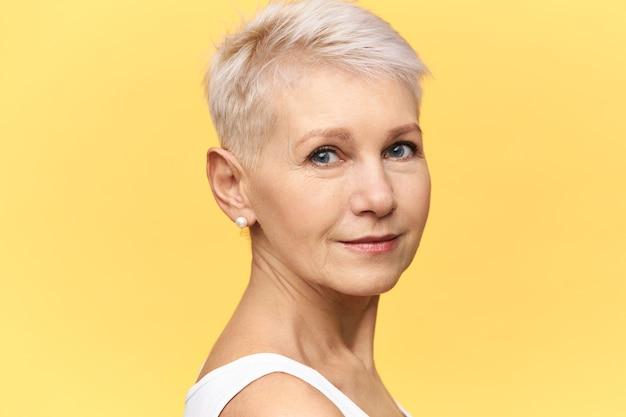 Metade da foto do perfil da bela mulher europeia de meia idade com olhos azuis, cabelo curto tingido e rugas no rosto, posando no estúdio, tendo olhar confiante.