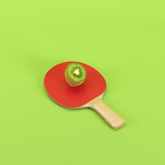 Metade da fruta de quivi madura na pá do ping pong isolada no fundo verde