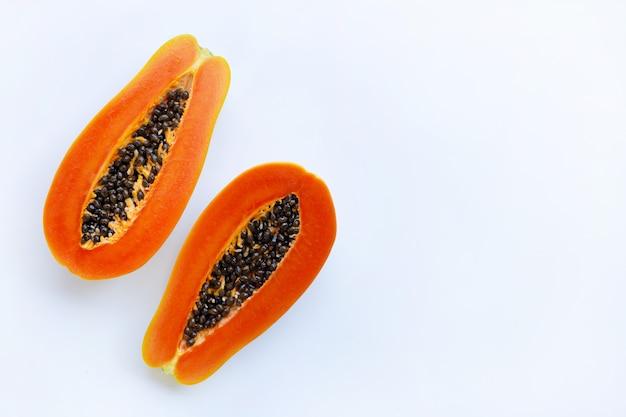 Metade da fruta madura do papaia com as sementes isoladas no fundo branco