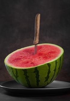 Metade da melancia com faca de melancia em fundo escuro