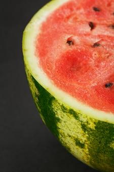 Metade da melancia vermelha saborosa e madura em um preto, textura de polpa suculenta de melancia vermelha madura com sementes. quadro vertical