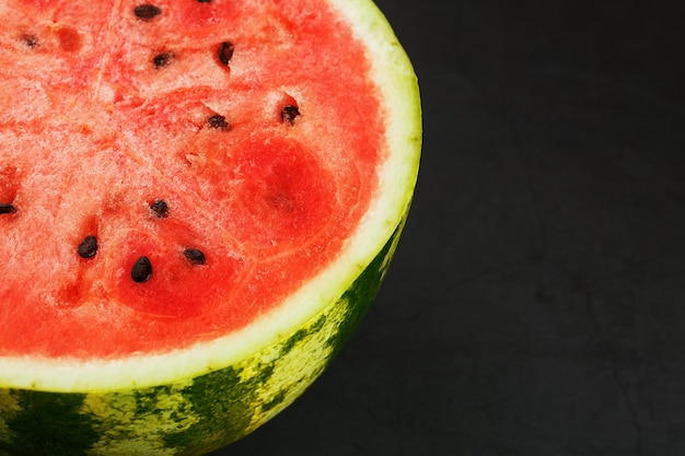 Metade da melancia vermelha saborosa e madura em um preto, textura de polpa suculenta de melancia vermelha madura com sementes