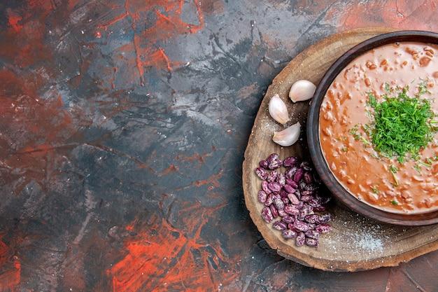 Metade da vista da sopa de tomate com alho e feijão na tábua de madeira na mesa de cores diferentes