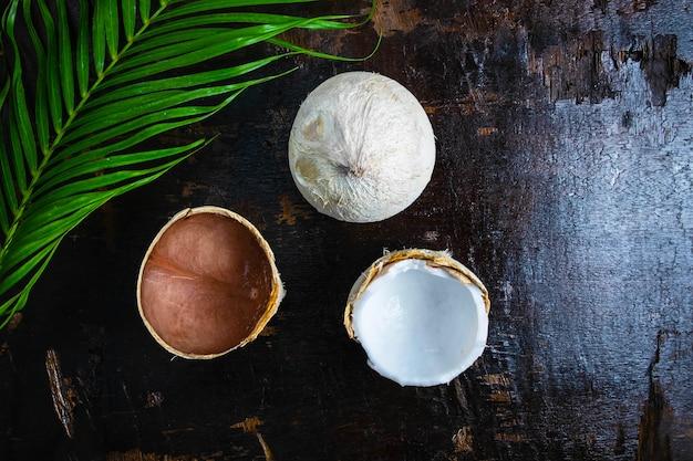 Metade de coco com folhas no fundo de madeira