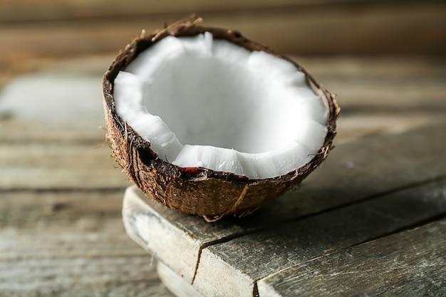 Metade de coco maduro na mesa de madeira