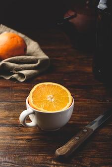 Metade de laranja em uma xícara branca sobre uma mesa rústica