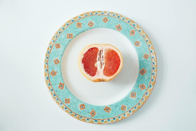 Metade de laranja no prato. de cima. comida saudável fitness.