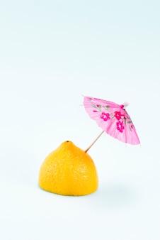 Metade de limão com guarda-chuva rosa no topo na luz de fundo