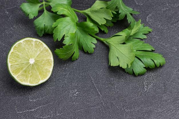 Metade de limão e raminho de salsa no preto. fundo vegetal. copie o espaço. vista do topo.