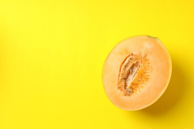 Metade de melão suculento em fundo amarelo