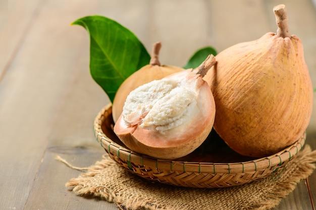 Metade de santol em fundo de madeira, santol tem gosto azedo e o meio de santol é mais doce. é uma fruta muito famosa da província de lopburi. tailândia