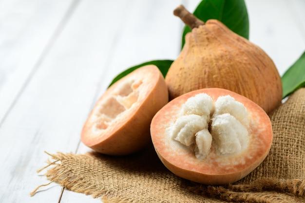 Metade de santol em um fundo de madeira branco, santol tem gosto azedo e o meio de santol é mais doce. é uma fruta muito famosa da província de lopburi. tailândia