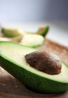 Metade de um abacate ao lado de dois pedaços cortantes de abacate.