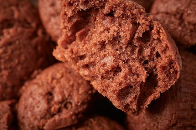 Metade de um bolinho de chocolate no fundo de outros, foco seletivo, close-up do fundo de comida