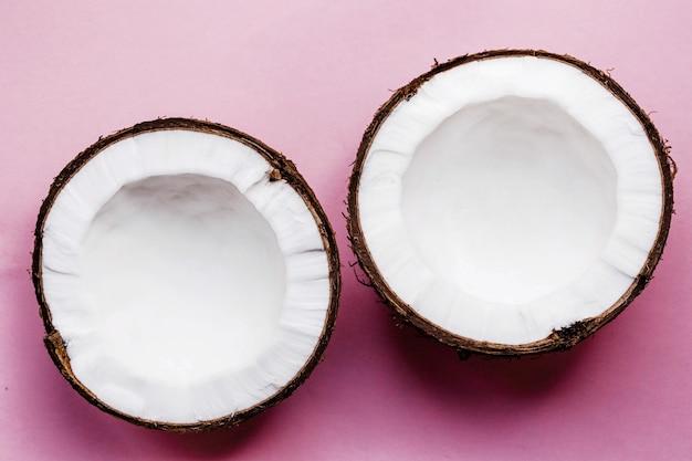 Metade de um coco fica no fundo rosa