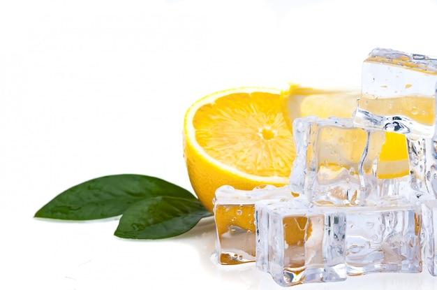 Metade de um limão fresco, brilhante, com folhas verdes e cubos de gelo frio