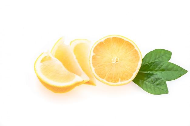 Metade de um limão fresco, limpo, brilhante, com folhas verdes e várias fatias cortadas em um fundo branco