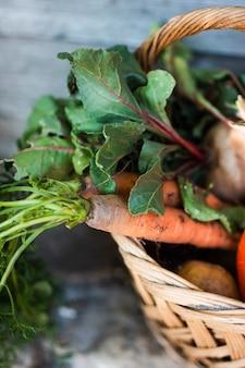 Metade de uma cesta com cenouras orgânicas e cesta com abóboras cenouras e rabanetes