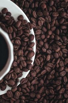 Metade de uma xícara de café preto quente sobre grãos de café torrados aromáticos frescos isolados no branco
