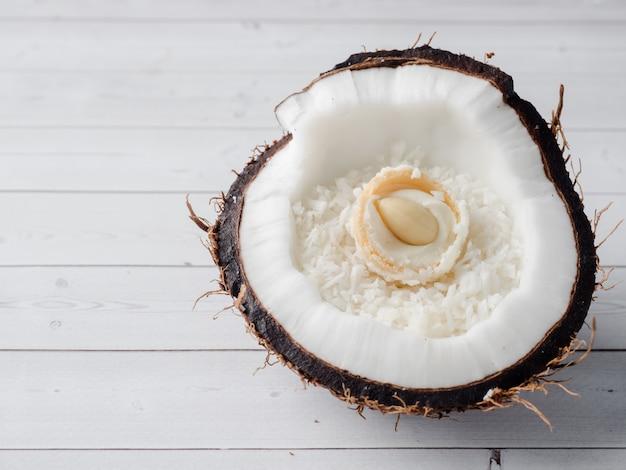 Metade do coco orgânico fresco com coco e doces de chocolate para dentro no fundo de madeira.