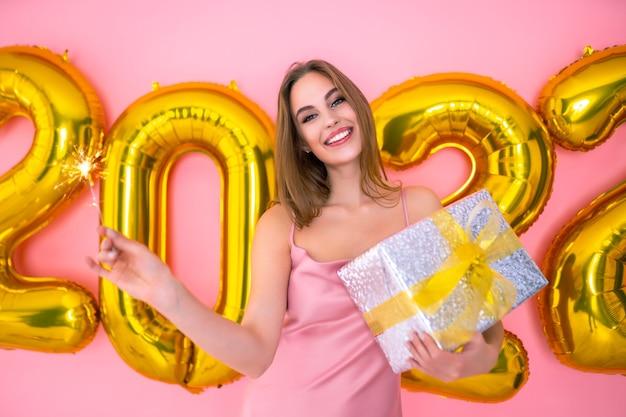 Metade do comprimento da menina santa animada segurando brilho e presente em balões de ar de mãos no ano novo