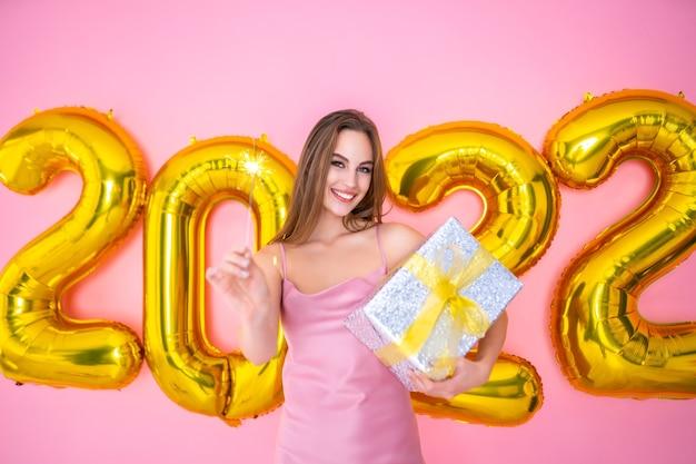Metade do comprimento da menina sorridente de papai noel com brilho e presente em balões de ar de mãos no ano novo