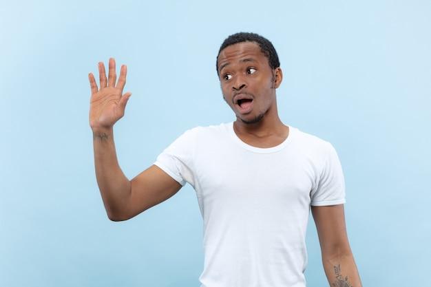 Metade do comprimento fechar o retrato de um jovem afro-americano de camisa branca na parede azul. emoções humanas, expressão facial, anúncio, conceito de vendas. encontrar alguém, cumprimentar, convidar.