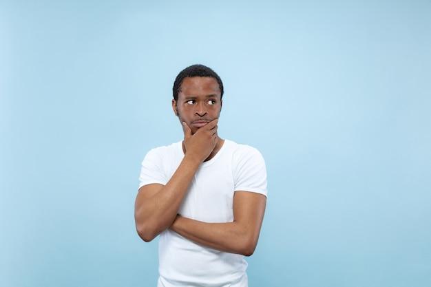 Metade do comprimento fechar o retrato de um jovem afro-americano de camisa branca na parede azul. emoções humanas, expressão facial, conceito de anúncio. pensativo, pensando cobrindo o rosto com as mãos.